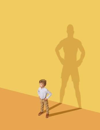 Ich könnte meine Familie beschützen. Zukünftiger Meister. Kindheit und Traumkonzept. Begriffsbild mit Kind und Schatten an der gelben Studiowand. Kleiner Junge möchte Boxer werden und eine Sportkarriere aufbauen. Standard-Bild