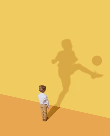 Champions goal is so close. Childhood and dream concept. Conceptual image with child and shadow on the yellow studio wall. Little boy want to become football player and to build a sport career. Imagens - 121063372