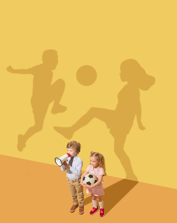 A true play without the rules. Pure emotions. Childhood and dream concept. Conceptual image with child and shadow on the yellow studio wall. Little boy and girl want to play football together. Stockfoto