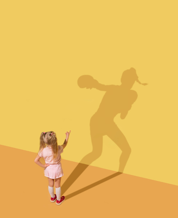 Finally hit to the uncertainty. Childhood and dream concept. Conceptual image with child and shadow on the yellow studio wall. Little girl want to become box player, sportswoman, champion, winner.