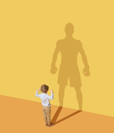 Ill be the strongest man. Future champion. Childhood and dream concept. Conceptual image with child and shadow on the yellow studio wall. Little boy want to become a boxer and to build a sport career.