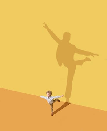 Flying higher. Childhood and dream concept. Conceptual image with child and shadow on the yellow studio wall. Little boy want to become ballet dancer, artist in theatre or businessman, office man. 免版税图像