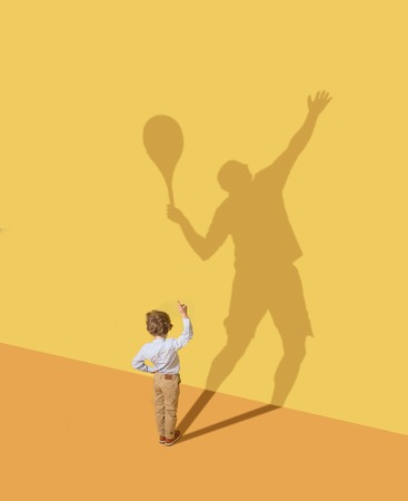 Getting best result in team. Childhood and dream concept. Conceptual image with child and shadow on the yellow studio wall. Little boy want to become tennis player and to build a sport career. 스톡 콘텐츠 - 121063406