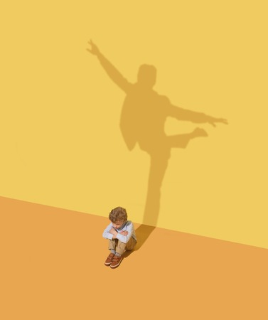 Flexibility. Childhood and dream concept. Conceptual image with child and shadow on the yellow studio wall. Little boy want to become ballet dancer, artist in theatre or businessman, office man.