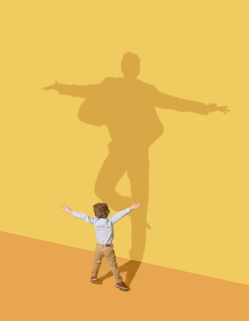 Succesfull. Childhood and dream concept. Conceptual image with child and shadow on the yellow studio wall. Little boy want to become ballet dancer, artist in theatre or businessman, office man. Banco de Imagens