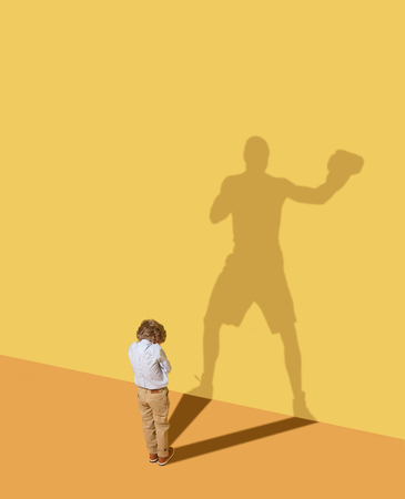 The kings hit to win. Future champion. Childhood and dream concept. Conceptual image with child and shadow on the yellow studio wall. Little boy want to become a boxer and to build a sport career.