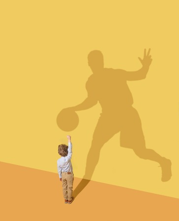 You can trust me. Childhood and dream concept. Conceptual image with child and shadow on the yellow studio wall. Little boy want to become basketball player and to build a sport career.