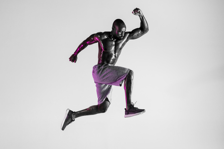 Win of the feelings. Young african-american bodybuilder training over grey studio background. Muscular single male model jumping in sportwear. Concept of sport, bodybuilding, healthy lifestyle. Stock Photo