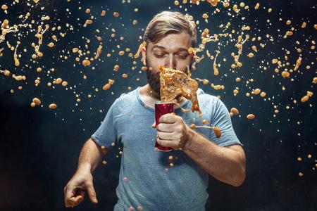 Mann trinkt eine Cola im Studio. Junger lächelnder glücklicher kaukasischer Kerl, der mit Cola öffnet und das Spray genießt Werbebild über Lieblingsgetränk. Lifestyle und menschliche Emotionen Konzept.