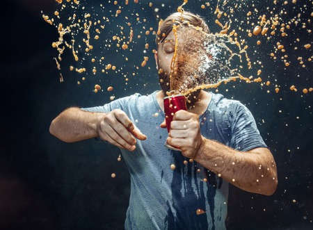 Man drinking a cola at studio. Young smiling happy caucasian guy opening can with cola and enjoying the spray. Advertising image about favourite drink. Lifestyle and human emotions concept.