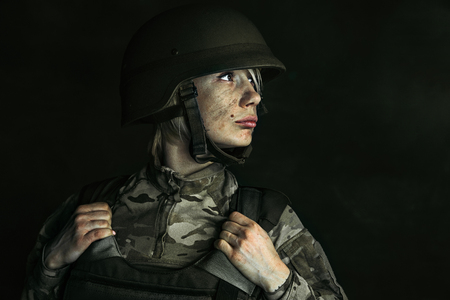 Looking for answers in surrounding world. Close up portrait of young female soldier. Woman in military uniform on the war. Depressed and having problems with mental health and emotions, PTSD. Stock Photo
