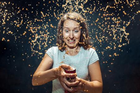 Donna che beve una cola allo studio. Giovane ragazza caucasica felice sorridente che apre lattina con cola e si gode lo spray. Immagine pubblicitaria sulla bevanda preferita. Stile di vita e concetto di emozioni umane. Archivio Fotografico