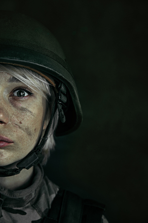 Terrible feeling of loneliness in a big world. Close up portrait of young female soldier. Woman in military uniform on the war. Depressed and having problems with mental health and emotions, PTSD.