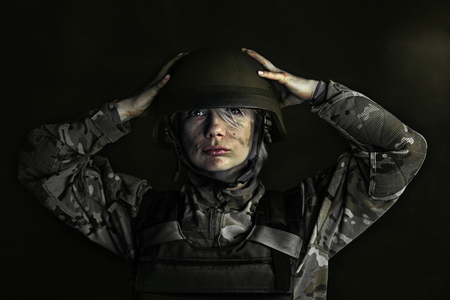 Protect your head and clear your mind. Close up portrait of young female soldier. Woman in military uniform on the war. Depressed and having problems with mental health and emotions, PTSD.