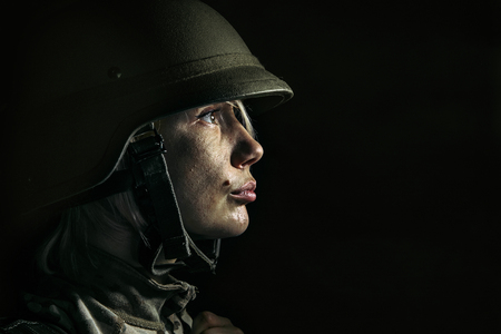 Hell on the earth is real and material. Close up portrait of young female soldier. Woman in military uniform on the war. Depressed and having problems with mental health and emotions, PTSD.