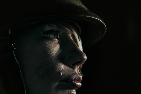 The pain is getting physical. Close up portrait of young female soldier. Woman in military uniform on the war. Depressed and having problems with mental health and emotions, PTSD.