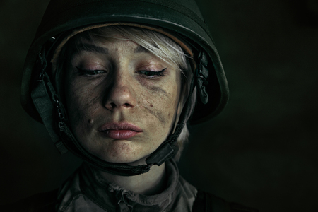 Hide the best of yourself for getting proud. Close up portrait of young female soldier. Woman in military uniform on the war. Depressed and having problems with mental health and emotions, PTSD.