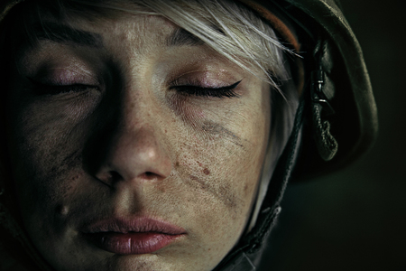 No tears and no fear anymore. Close up portrait of young female soldier. Woman in military uniform on the war. Depressed and having problems with mental health and emotions, PTSD.
