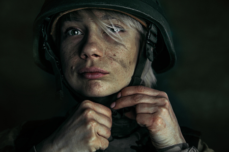 Preparing for being stronger like a stone. Close up portrait of young female soldier. Woman in military uniform on the war. Depressed and having problems with mental health and emotions, PTSD.