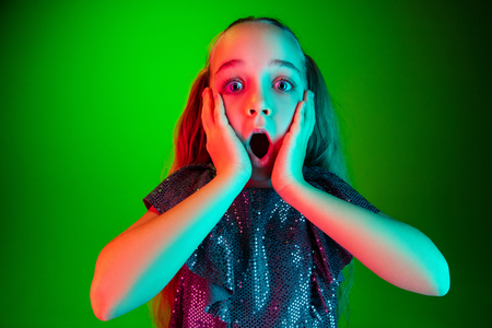 Wow. Beautiful female half-length portrait over green neon lights studio backgroud. Young emotional surprised teen girl standing with open mouth. Human emotions, facial expression concept. Trendy colors Standard-Bild