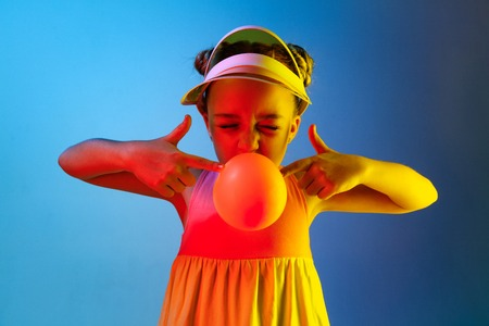 Young girl blowing bubble gum. Happy teen girl standing over trendy blue neon studio background. Beautiful female portrait. Young satisfy girl. Human emotions, facial expression, summer holidays concept. 免版税图像 - 121278387