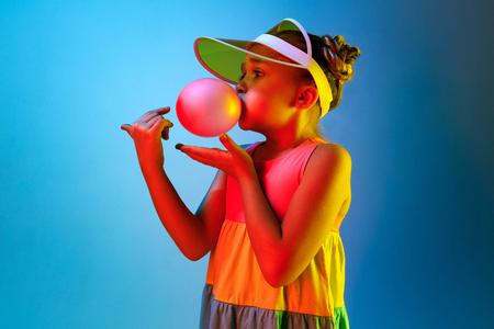 Junges Mädchen bläst Kaugummi. Glückliches jugendlich Mädchen, das über modischem blauem Neonstudiohintergrund steht. Schönes weibliches Portrait. Junge befriedigen Mädchen. Menschliche Emotionen, Gesichtsausdruck, Sommerferienkonzept.