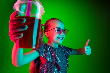 Happy teen girl standing and smiling with cola isolated on trendy green lights neon studio background. Beautiful female portrait. Young satisfy girl. Human emotions, facial expression, summer holidays concept. Standard-Bild