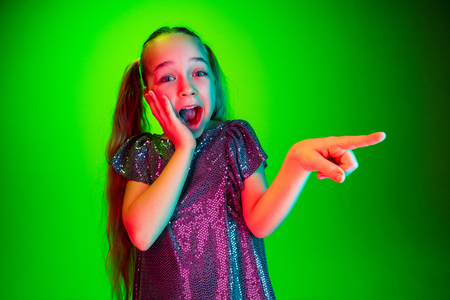 Wow. Beautiful female half-length portrait pointing to left over green lights neon studio backgroud. Young emotional surprised teen girl standing with open mouth. Human emotions, facial expression concept. Trendy colors