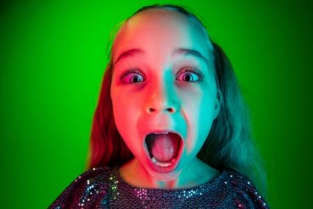 Beeindruckend. Schönes weibliches Halbfigurenporträt über Neonstudiohintergrund der grünen Lichter. Junges emotionales überraschtes jugendlich Mädchen, das mit offenem Mund steht. Menschliche Emotionen, Gesichtsausdruckkonzept. Trendige Farben