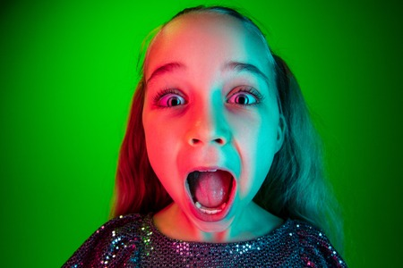 Wow. Beautiful female half-length portrait over green lights neon studio backgroud. Young emotional surprised teen girl standing with open mouth. Human emotions, facial expression concept. Trendy colors