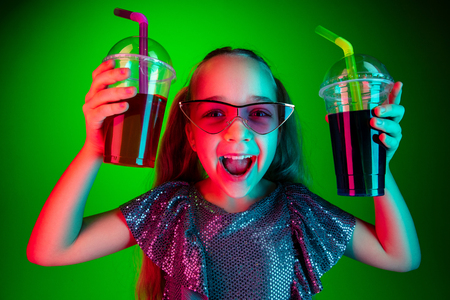 Happy teen girl standing and smiling with cola isolated on trendy green lights neon studio background. Beautiful female portrait. Young satisfy girl. Human emotions, facial expression, summer holidays concept. Stock Photo