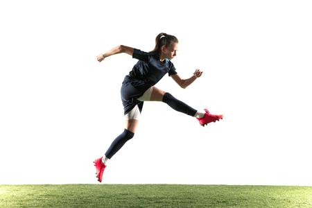 Jugador de fútbol o fútbol femenino joven con el pelo largo en ropa deportiva y botas pateando la pelota para el gol en salto aislado sobre fondo blanco. Concepto de estilo de vida saludable, deporte profesional, afición.