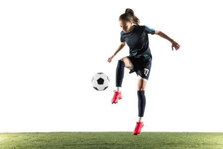 Young female football or soccer player with long hair in sportwear and boots kicking ball for the goal in jump isolated on white background. Concept of healthy lifestyle, professional sport, hobby. Imagens
