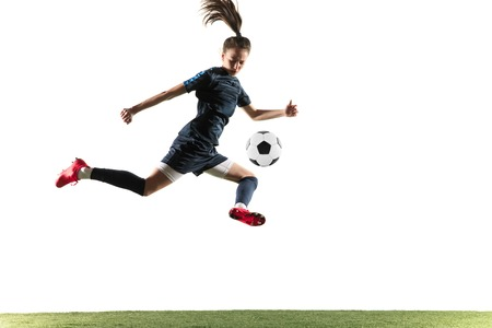 Young female football or soccer player in sportwear and boots kicking ball for the goal in jump isolated on white background. Concept of healthy lifestyle, professional sport, hobby.