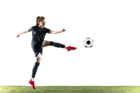 Joven futbolista o futbolista con pelo largo en ropa deportiva y botas pateando la pelota para el gol en salto aislado sobre fondo blanco Concepto de estilo de vida saludable, deporte profesional, afición.