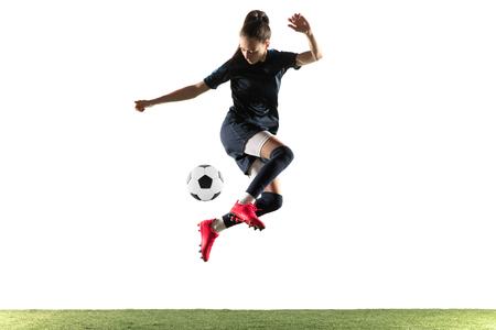 Giovane calciatore femminile o giocatore di football americano con capelli lunghi in abbigliamento sportivo e stivali che danno dei calci alla palla per l'obiettivo nel salto isolato su fondo bianco. Concetto di stile di vita sano, sport professionistico, hobby.