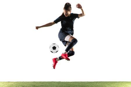 Young female soccer or football player with long hair in sportwear and boots kicking ball for the goal in jump isolated on white background. Concept of healthy lifestyle, professional sport, hobby. Stok Fotoğraf - 121278554