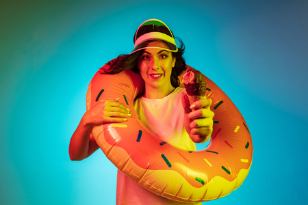 Happy young woman in a cap and in a rubber ring with an icecream on trendy blue neon studio background. Female portrait. Concept of human emotions, facial expression, summer holidays or weekend.