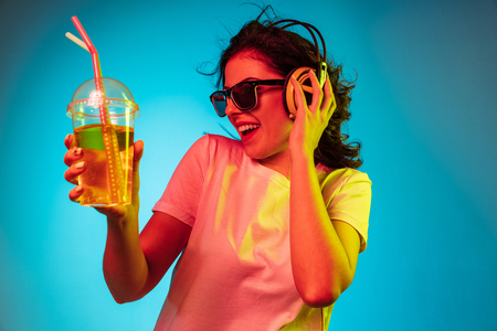 Happy young woman dancing and smiling in headphones over trendy blue neon studio background. Beautiful female portrait. Concept of human emotions, facial expression, summer holidays or weekend.