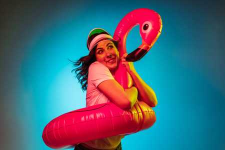 Happy young woman in a cap and in a rubber flamingo over trendy blue neon studio background. Beautiful female portrait. Concept of human emotions, facial expression, summer holidays or weekend. 版權商用圖片