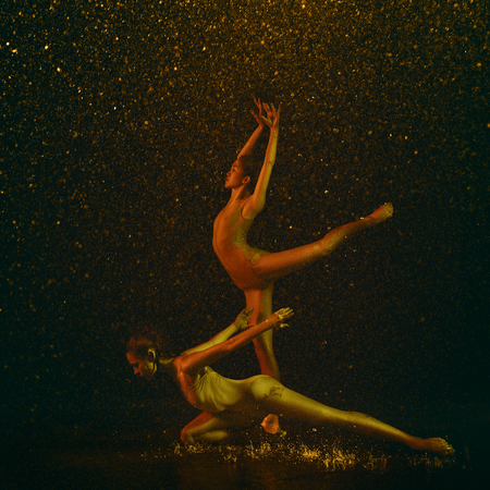 Marvelous. Two young female ballet dancers under water drops and spray. Caucasian and asian models dancing together in neon lights. Ballet and contemporary choreography concept. Creative art photo. Banque d'images