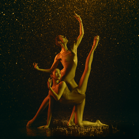 Higher. Two young female ballet dancers under water drops and spray. Caucasian and asian models dancing together in neon lights. Ballet and contemporary choreography concept. Creative art photo. Reklamní fotografie