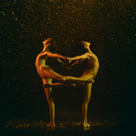 Stronger. Two young female ballet dancers under water drops and spray. Caucasian and asian models dancing together in neon lights. Ballet and contemporary choreography concept. Creative art photo.