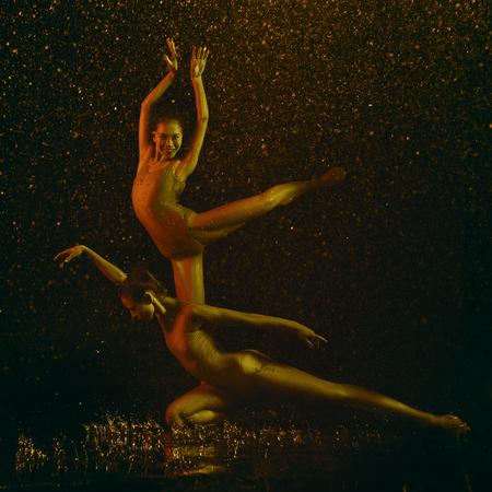 Le sourire. Deux jeunes danseuses de ballet sous les gouttes d'eau et les embruns. Des modèles caucasiens et asiatiques dansent ensemble dans des néons. Concept de ballet et de chorégraphie contemporaine. Photo d'art créatif.