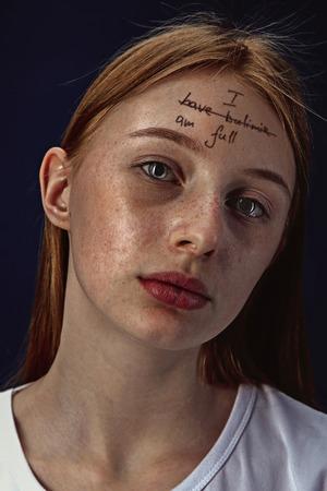 Ritratto di giovane donna con problemi di salute mentale. L'immagine di un tatuaggio sulla fronte con le parole I have bulimia-Im full.Concetto di nascondere i veri sentimenti, problemi psicologici, trattamento.