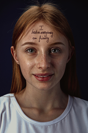 Portrait of young woman overcoming mental health problems. The image of a tattoo on the forehead with the words I hate everybody-friendly. Concept of rehabilitation, return to healthy lifestyle.