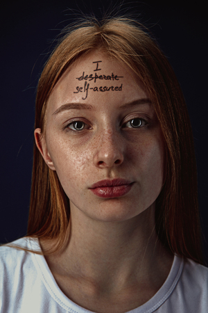 Portrait of young woman with mental health problems. The image of a tattoo on the forehead with the words I desperate self-assured. Concept of hidding the true feelings, psycological trouble. Stockfoto