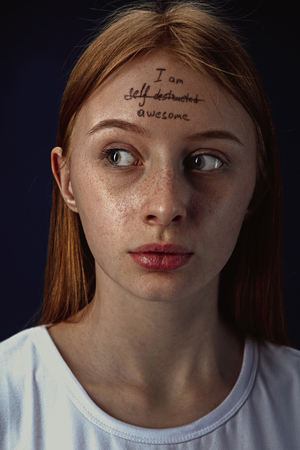 Portrait of young woman with mental health problems. The image of a tattoo on the forehead with the words Im self-destructed-awesome. Concept of hidding the true feelings, psycological trouble. 写真素材