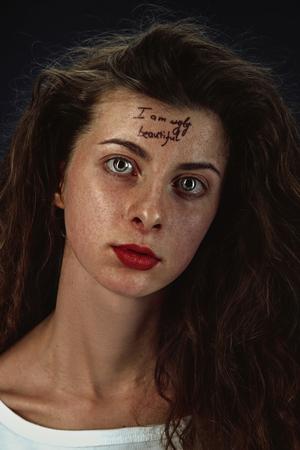 Portret van een jonge vrouw met psychische problemen. De afbeelding met de tatoeage op het voorhoofd met de woorden ik ben lelijk-mooi. Concept van het verbergen van de ware gevoelens, psychische problemen, behandeling.