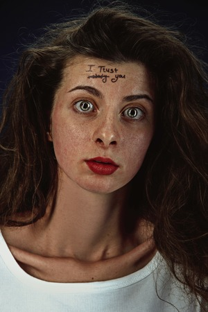 Portrait of young woman with mental health problems. The image of the tattoo on the forehead with the words I trust nobody-you. Concept of hidding the true feelings, psycological trouble, treatment. Stockfoto
